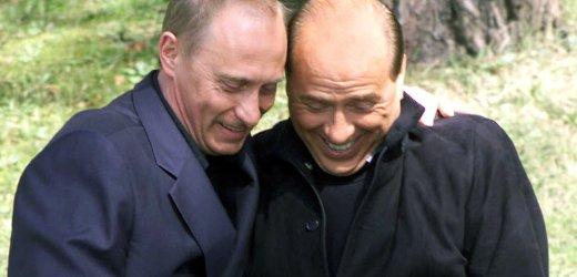 Russian President Vladimir Putin (L) presents Italian Prime Minister Silvio Berlusconi with a book p..